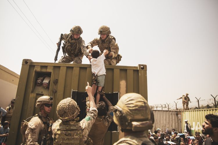 UK coalition forces, Turkish coalition forces, and US Marines assist a child during an evacuation at Hamid Karzai International Airport, Kabul, Afghanistan 200821 CREDIT US DEPARTMENT OF DEFENSE