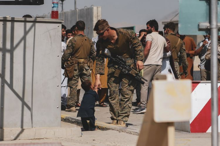 US Marine plays with a child during an evacuation at Hamid Karzai International Airport, Kabul, Afghanistan 210821 CREDIT US DEPARTMENT OF DEFENSE